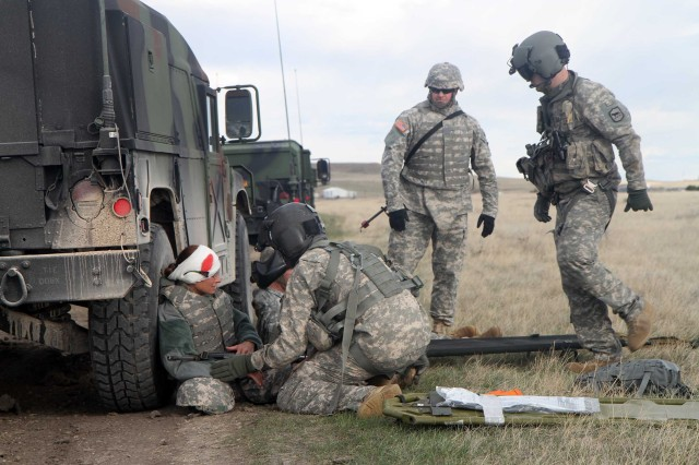 Flight medics with Company C, 1st Battalion, 189th Aviation Regiment, South Dakota Army National Guard, aid a simulated injured Soldier during a collective training exercise at Orman Dam, near Belle Fourche, S.D., April 5, 2017. The training event was held in connection with members of the 881st Troop Command and allowed the units to work together to practice medical evacuation procedures and response times for future operations involving realistic combat scenarios.