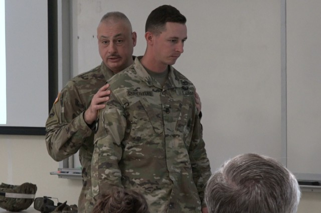 Sgt. 1st Class Geoffrey Davis (left) demonstrates the proximity of the second Soldier in a stack during explosives training. Staff Sergeant Christopher Dupertuis (right) would be holding a blast blanket the size of a door in front of himself in a live explosives training environment. When a blast occurs in front of the stack, each Soldier experiences an exponentially larger hit from an explosion's pressure wave the farther back they are in the stack.