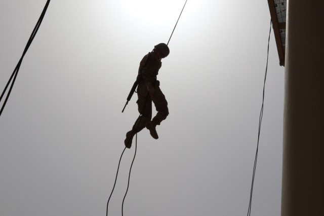 A U.S. Servicemember navigates the rappel tower during day eight of U.S. Army Central's first Air Assault Course, April 12, 2017, at Camp Buehring, Kuwait. The 50-foot rappel tower is one test within the three-phase course soldiers have to pass to attain the air assault badge. The Air Assault Course is a 12-day class that allows U.S. military personnel in the U.S. Army Central area of operations the unique opportunity to become air assault qualified, while deployed outside the continental United States.