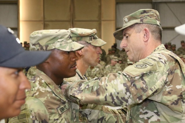 U.S. Army Maj. Gen. William Hickman (right), deputy commanding general of U.S. Army Central, pins air assault wings on one of the Air Assault Course's honor graduates Sgt. Carl Howard, combat medic, 215th Brigade Support Battalion, 3rd Armored Brigade Combat Team, 1st Cavalry Division, during graduation day, April 14, 2017, at Camp Beuhring, Kuwait. The Air Assault Course is a 12-day class that allows U.S. military personnel in the U.S. Army Central area of operations the unique opportunity to become air assault qualified, while deployed outside the continental United States.