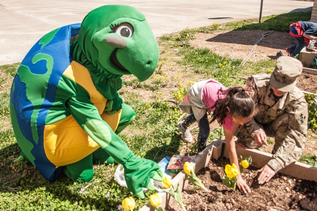 Clean Water Casey and Combat Training Company Soldiers helps students at East Elementary School on Fort Leonard Wood plant a variety of flowers around the school in honor of Earth Day.