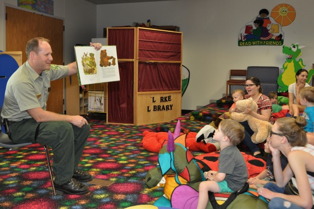 Greg Painter of the Mark Twain National Forest, U.S. Forest Service, reads the original Smokey the Bear book to children at  the Bruce C. Clarke Library story time April 19.