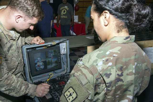 Spc. Brad McDowell, an Emergency Ordnance Disposal specialist with the 55th EOD Company, shows Sgt. Valerie Booker, from the 369th Adjutant General Battalion how to pilot the Talon remotely operated vehicle.
