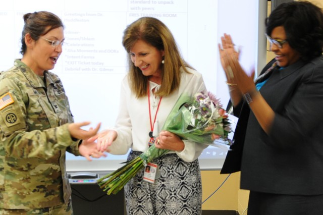 Col. Shannon T. Miller, Fort Rucker garrison commander, presents Dr. Vicki Gilmer, DODEA Americas Elementary Principal of the Year and Fort Rucker Schools principal, a garrison commander's coin as Dr. Lisa Coleman, DODEA Georgia/Alabama community superintendent looks on April 14.