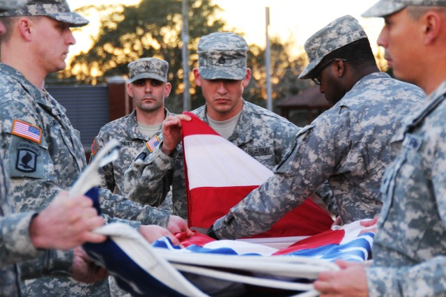 "NCO Academy Soldiers fold the flag during the ""Retreat"" ceremony on Howze Field in this file photo."