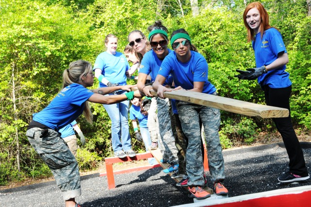 Spouses work together to set a board down to help their team traverse an obstacle at the Leaders Reaction Course during Spouses' Aviation Day April 13.