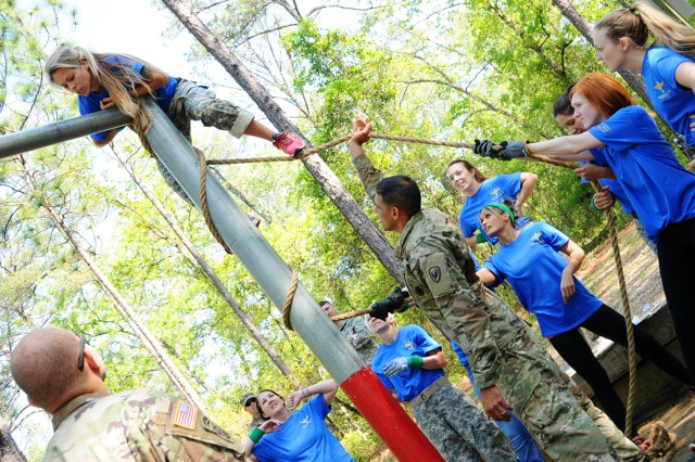 Amanda Crowley, military spouse, climbs her way up an obstacle as her team helps steady her ascent.
