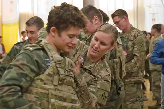 Staff Sgt. Kacie Reed, Medical Platoon Sergeant, 3rd Bn., 29th FA Reg., 3rd ABCT, 4th ID shows a student how to connect the shoulder latches on her Improved Outer Tactical Vest at the uniformed school career fair in Zielona Gora, Poland April 20, 2017. 3rd Bn., 29th FA Reg., priority is to sustain interoperability with the Polish Army, however, integrating U.S. Soldiers into local events helps strengthen relationships within Polish communities. (Photo by Army Sgt. Justin Geiger, 7th Mobile Public Affairs Detachment)