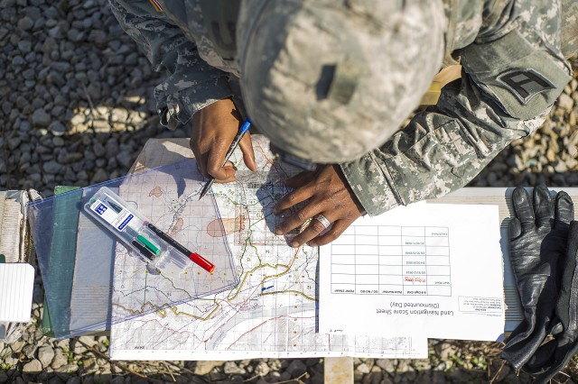 Staff Sgt. Tyron Wade, an observer coach/trainer from 2nd Battalion, 305th Field Artillery Regiment, 177th Armored Brigade, plots his first navigation points on a map during the land navigation event at the First Army Division East fourth-quarter Best Warrior Competition, April 10, 2017 at Fort Knox, Ky. Wade and five other competitors competed head-to-head in multiple events over the course of three days, pushing themselves to the edges of their physical and mental limitations.