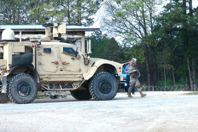 Soldiers from the 1st Brigade Combat Team (BCT), 10th Mountain Division (Light Infantry) patrol next to a Mine-Resistant Ambush-Protected All-Terrain Vehicle with a Soldier Network Extension during the BCT's Joint Readiness Training Center rotation at Fort Polk, Louisiana, March 18, 2017.