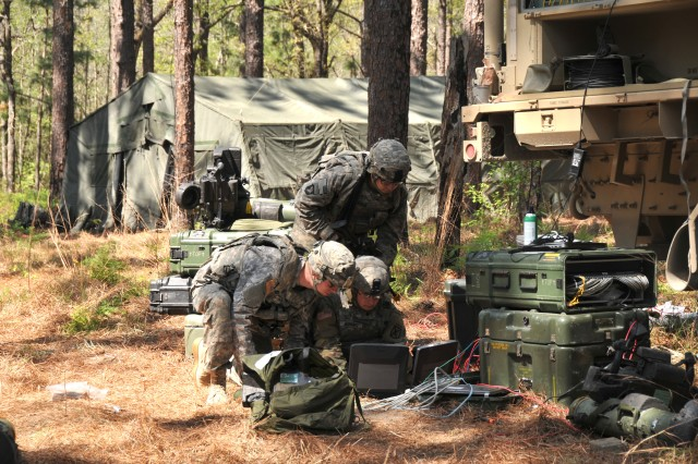Soldiers from the 1st Brigade Combat Team (BCT), 10th Mountain Division (Light Infantry) work on laptops next to a Tactical Communication Node during the BCT's Joint Readiness Training Center rotation at Fort Polk, Louisiana, March 20, 2017.