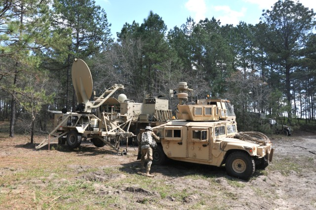 A Soldier from the 1st Brigade Combat Team (BCT), 10th Mountain Division (Light Infantry) exits a Humvee next to a Tactical Communication Node (background) and Satellite Transportable Terminal Plus during the BCT's Joint Readiness Training Center rotation at Fort Polk, Louisiana, March 20, 2017.