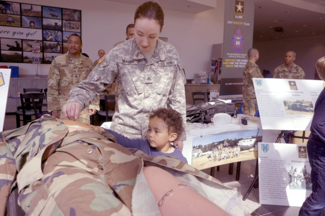 KAISERSLAUTERN, Germany - Sgt. Pattisue Graham, a member of the Medical Support Unit - Europe, explains a CPR mannequin to a child Friday, April 21 at the Kaiserslautern Military Community Center on Ramstein Air Base. Her units, part of the Army Reserve's 7th Mission Support Command, was celebrating the 109th Army Reserve birthday during the event.