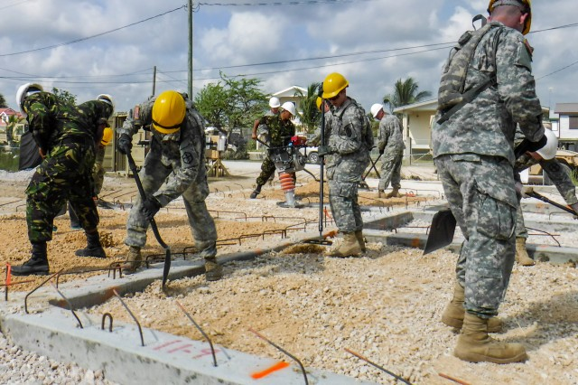 Soldiers assigned to the 672nd Engineer Company, 301st Maneuver Enhancement Brigade, from Missoula, Montana, work with soldiers with the Belize Defense Force to spread and compact gravel to ensure a solid base at the Ladyville Health Clinic in Ladyville, Belize. The soldiers were deployed to Belize in support of Beyond the Horizon, U.S. Army South and U.S. Southern Command's annual multinational humanitarian and civic assistance program (Courtesy Photo).