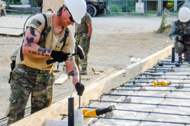 Sgt. Timothy Augustin of the 672nd Engineer Company, 301st Maneuver Enhancement Brigade, drives a piece of rebar in a pre-drilled hole, which will be used to hold the concrete slab to the footers at the Ladyville Health Clinic, Ladyville, Belize. The soldiers were deployed to Belize in support of Beyond the Horizon, U.S. Army South and U.S. Southern Command's annual multinational humanitarian and civic assistance program (Courtesy Photo).
