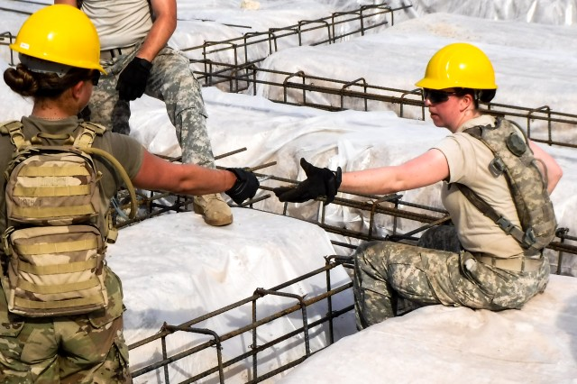Pvt. Jade Smith of the 672nd Engineer Company, left, hands a pair of pliers to Spc. Haley Goodin as she ties together rebar at the Double Head Cabbage Health Clinic, in Double Head Cabbage, Belize, April 1, 2017. The soldiers were deployed to Belize in support of Beyond the Horizon, U.S. Army South and U.S. Southern Command's annual multinational humanitarian and civic assistance program (Courtesy Photo).