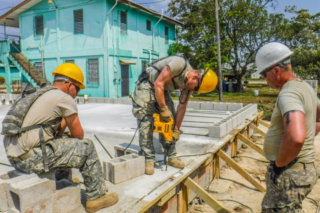 Soldiers assigned to the 672nd Engineer Company, 301st Maneuver Enhancement Brigade, from Missoula Montana, drill holes into a concrete slab that will be used to hold the walls together at the Ladyville Health Clinic, Ladyville, Belize. The soldiers were deployed to Belize in support of Beyond the Horizon, U.S. Army South and U.S. Southern Command's annual multinational humanitarian and civic assistance program (Courtesy Photo).