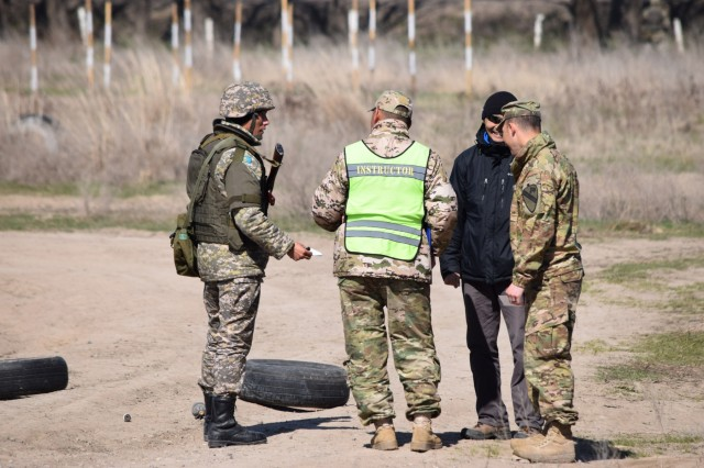 A Kazakhstani instructor from the Kazakhstan Peacekeeping Battalion, center, and an observer from the U.S. Army, right, hand a casualty card to a Kazakhstani soldier during a scenario for Steppe Eagle Koktem Apr. 10, 2017, at Illisky Training Center, Kazakhstan.