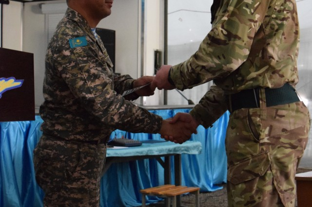 Lt. Col. Bulat Dusembayev, commander of the Kazakhstan Peacekeeping Brigade, left, presents Cpl. Christopher Meek, 1st Battalion, The Rifles, 160 Brigade, with a certificate of appreciation during the closing day of Steppe Eagle Koktem, Apr. 11, 2017, at Illisky Training Center, Kazakhstan.