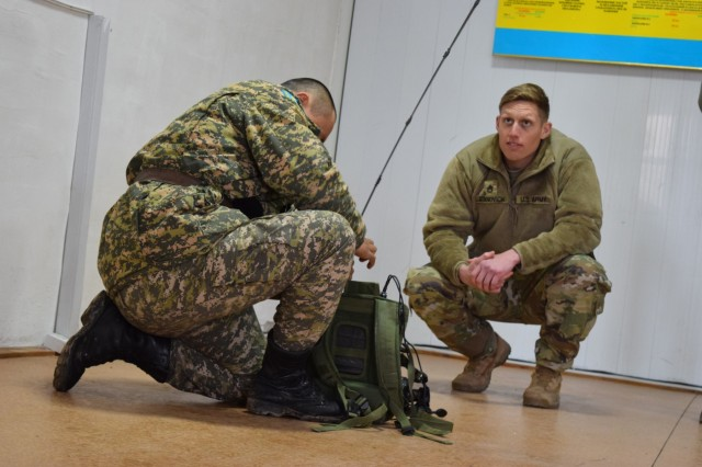 Staff Sgt. Joshua Atanovich, 149th Military Engagement Team, watches the time as a Kazakhstani soldier from the Kazakhstan Peacekeeping Battalion prepares his radio for a commo check during Steppe Eagle Koktem, Apr. 4, 2017, at Illisky Training Center, Kazakhstan. Tactical communications is one of the military-to-military engagements that occur during Steppe Eagle Koktem.