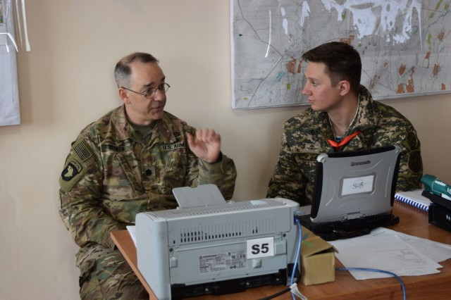 Lt. Col. James Becker, 352nd Civil Affairs Command, discusses civil military operations with a Kazakhstani soldier of the Kazakhstan Peacekeeping Battalion during day two of Steppe Eagle Koktem, Apr. 2, 2017, at Illisky Training Center, Kazakhstan.