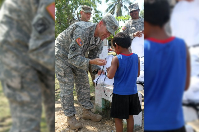 Army Sgt. 1st Class Eric Ritchey, a team leader with the 413th Civil Affairs Battalion, hands out school supplies to children at the Liberty Children's Home in Ladyville, Belize, April 18, 2017. Ritchey and other U.S. soldier participated in the community relations event as part of Beyond the Horizon 2017.