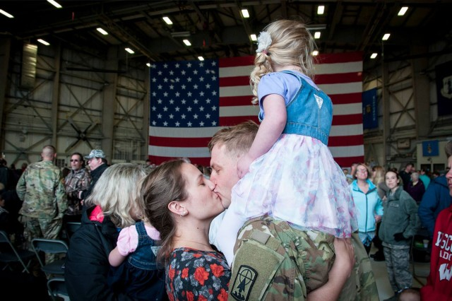 A Soldier and his wife embrace as their daughter looks over a crowd of families reuniting for the first time in nearly a year April 13, 2017. Soldiers from the 32nd Military Police Company return home after being deployed to U.S. Naval Station Guantanamo Bay, Cuba.