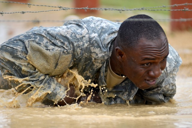 Sgt. Francis Danso slithers through muddy waters to avoid getting snagged during an obstacle course challenge as part of the Army Medicine Regional Health Command-Central's Best Warrior competition, held April 10-14 at Fort Hood, Texas, and hosted by Carl R. Darnall Army Medical Center. Danso, representing Irwin Army Community Hospital, Fort Riley, Kan., earned top honors in both the physical fitness test and the combined written test and essay event. Originally from Africa, Danso's hometown is Brooklyn Center, Minn.