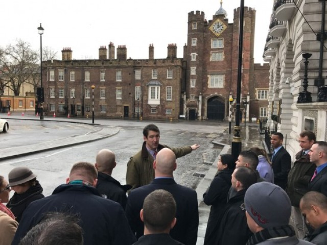 U.K. Maj. Charlie Sprake shares historic information about landmarks with fellow students during a London tour, including St. James Place, a residence of the royal family, during a field trip. The U.K