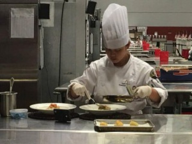 Spc. Anne Nicole Yapcengo, 307th Expeditionary Signal Battalion, focuses on preparing her main course for the judging event of the competition.