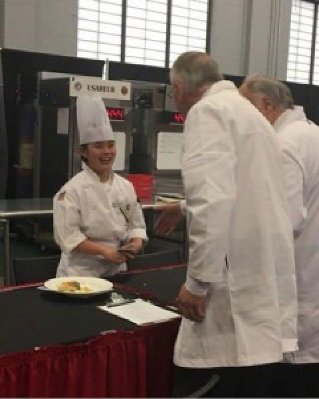 Spc. Anne Nicole Yapcengo, 307th Expeditionary Signal Battalion, meets with judges to critique her prepared dish.