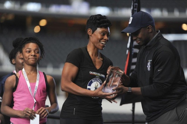 Dallas Cowboy's Manager Terrence Wheatley presents Sgt. 1st Class Shonta Tucker with the 1st place award for completing the Dallas Cowboys Military Combine while her daughters, Brianna and Asia, look on.