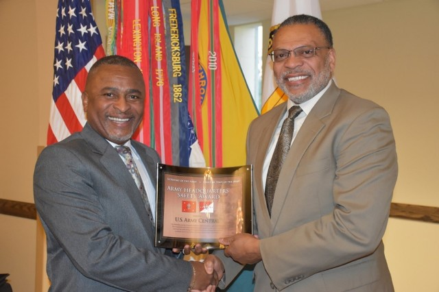 Eugene Collins (left), deputy assistant secretary of the Army (Environment, Safety and Occupational Health), presents the Fiscal 2016 Secretary of the Army and Chief of Staff, Army Headquarters Safety Award, to Norvel Turner, senior safety director, U.S. Army Central. As the higher headquarters, Turner accepted additional awards on behalf of the 1st Sustainment Command (Theater), 513th Military Intelligence (Theater) and Headquarters, Headquarters Battalion, USARCENT. (U.S. Army photo by Luis Martinez)
