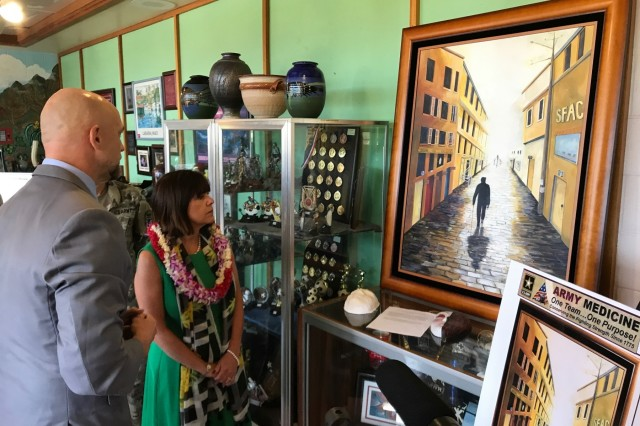 SCHOFIELD BARRACKS, Hawaii (April 24, 2017) --- The Second Lady of the United States, Karen Pence, views a painting created by a spouse of a 25th ID Soldier, Cindy Manga. The painting depicts a shadowed figure, a Soldier with a cane walking down a dark hallway. As the hallway goes on, it gets lighter. At the end of the tunnel is the source of the light: the Soldier's wife and two children awaiting him and supporting him through his journey. On the left side wall in the scene are rooms with each department that helped the family through. On the right, a sign that reads: SFAC, which stands for Soldier and Family Assistance Center. Pence also visited with military and civilian leaders during a tour hosted by U.S. Health Clinic at Schofield Barracks, to talk about how art therapy is being used to help military members and their families deal with difficulties, disabilities or diagnoses. The tour took place outside of the clinic's walls to where art therapists and patients have unfettered access to their tools: Pens, paper, brushes, ceramics and more. Pence, who is a champion for art therapy programs, visited the arts and crafts building on Schofield, where she spoke with patients currently enrolled in art therapy programs.