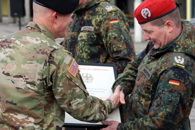 U.S. Army Col. Jeff Worthington, commander of 2nd Theater Signal Brigade, presents a partnership certificate to German Army Lt. Col. Michael Mensching, commander of the 282nd CIS Support Battalion, Bundeswehr Communications and Information Systems Command, at a partnership formalization ceremony April 25, 2017 in Bonn, Germany.