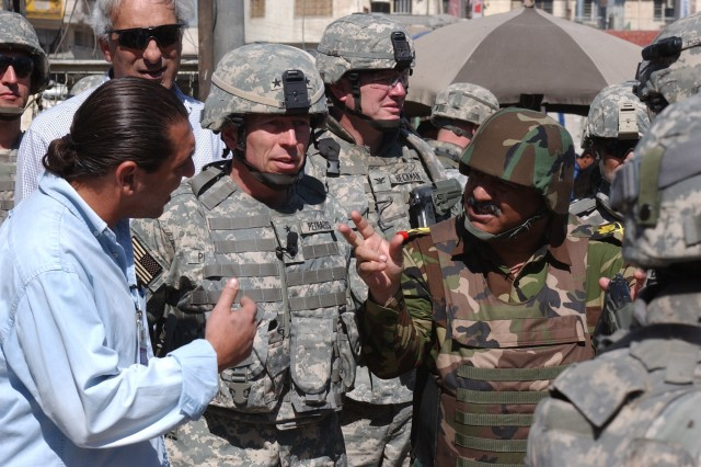 Gen. David Petraeus (second from left, commander of Multi-National Force-Iraq, walks through the Al Shurja Market in eastern Baghdad on March 11, 2007, accompanied by an Iraqi division commander, staff and journalists.