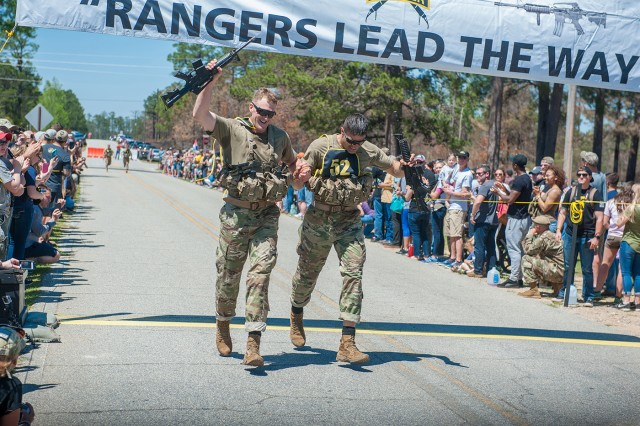 Teammates 1st Lt. Andy Harvey, left, and Capt. Tim Cox cross the finish line following the final event of the 2017 David E. Grange Jr. Best Ranger Competition April 9. Cox said the chemical officers maintained a steady pace in the three-day competition to help them finish 6th overall against tough competition. Photo courtesy of Fort Benning Public Affairs
