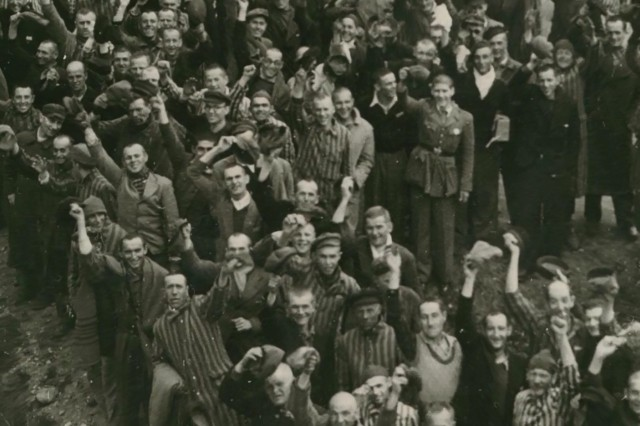 Holocaust survivors rejoice as the Army's 45th Infantry Division liberates about 30,000 prisoners at Dachau, Germany, April 1945.