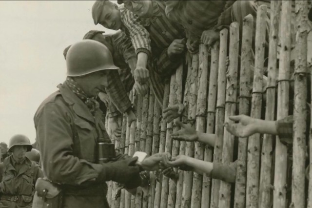 Soldiers of the 45th Infantry Division liberate prisoners at Dachau, Germany, and hand out food in April 1945.