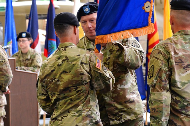 Lt. Col. Beau Tibbitts, 1st Battalion, 58th Aviation Regiment (Airfield Operations) commander, accepts the unit colors from Col. Michael E. Demirjian, Air Traffic Services Command and 164th Theater Airfield Operations Group commander, as he assumes command from Lt. Col. James Ashburn during a change of command ceremony at the U.S. Army Aviation Museum April 19.