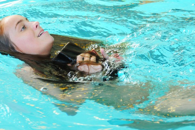 Addison Nix, civilian, swims with a 10-pound weight on her chest during a prerequisite skills check for a lifeguard certification course April 21.