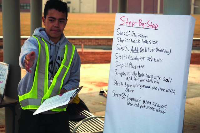 Eagle Scout candidate Raymond Santiago provided a thorough safety briefing before volunteers began to plant trees at the small park next to the Humphreys High School athletic fields on April 1.