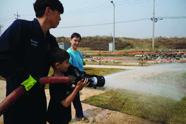 Humphreys Fire Fighter So, Myong Sok (left) was part of the fire crew who helped water the sod at Raymond Santiago's Eagle Scout project on April 8. Also shown are Keegan and Devlin Welsh.