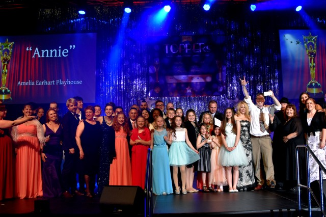 """Lt. Gen. Ben Hodges, Commanding General U.S. Army Europe, presents the cast and crew of U.S. Army Garrison Wiesbaden's Amelia Earhart Playhouse's production of """"Annie"""" the award for Best Musical at the 2017 Toppers, April 29 at the U.S. Army Garrison Wiesbaden Sports, Fitness and Outdoor Recreation Center."""