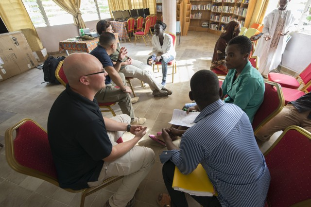 Staff Sgt. Brandon Collins, bottom left, a member of the 83rd Civil Affairs Battalion's Team 8321, and other Soldiers chat with Cameroonians inside the American Corner in Garoua, Cameroon, April 24, 2017. Each week, Soldiers assigned to Task Force Toccoa, a 101st Airborne Division-led unit, visit the cultural center to interact with locals.