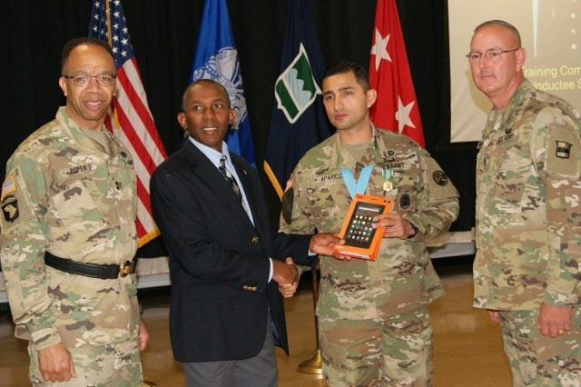 Retired Sgt. Maj. Gary Lyons (second from left) presents Sgt. 1st Class Daniel Aparicio with a Kindle Fire tablet as a gift at Aparicio's Sgt. Audie Murphy Club induction ceremony held at Fort Devens, Massachusetts, April 6, 2017. Maj. Gen. A.C. Roper (left), commander of the 80th Training Command, and Command Sgt. Maj. Jeffrey Darlington (right), 80th TC senior enlisted leader, pose for pictures with Lyons and Aparicio.