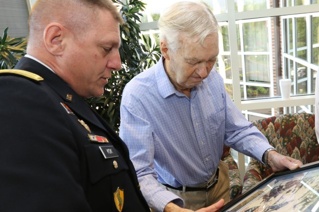 Maj. Gen. Troy D. Kok, commanding general of the U.S. Army Reserve's 99th Regional Support Command, presents framed artwork from World War II to Claude Hodges, a 99th Infantry Division veteran who served during the Battle of the Bulge and is currently a resident at the Virginia Veterans Care Center in Roanoke, Virginia. Kok visited Hodges and other veterans at the center April 28.