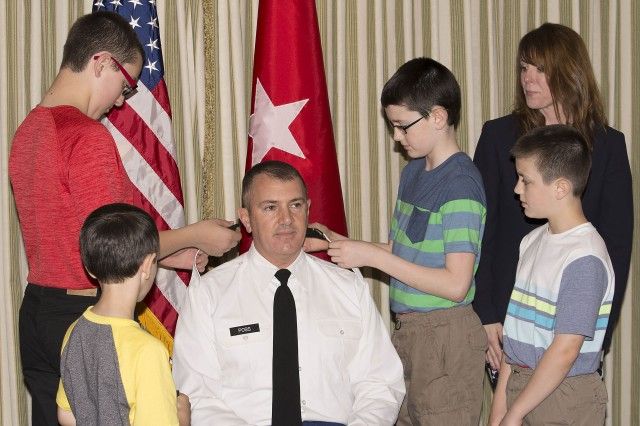Col. Michael Poss' sons replace the epaulettes on the shoulder loops of his shirt with the rank of colonel. (Photo by Capt. Lonnie Collier, ASC Public Affairs)