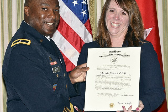 """Dawn Poss displays her honorary promotion orders making her a brigadier general and recognizing her as """"The One In Charge"""" at the Poss family home known as """"Household 6"""". Assisting her is Brig. Gen. Norman Green. (Photo by Capt. Lonnie Collier, ASC Public Affairs)"""