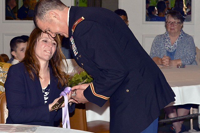 Col. Michael Poss presents his wife, Dawn, flowers for his appreciation for her steadfast support during his career. (Photo by Capt. Lonnie Collier, ASC Public Affairs)